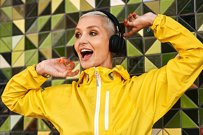 Buy stock photo Cropped shot of an attractive young woman standing against a wall and dancing while listening to music through her headphones