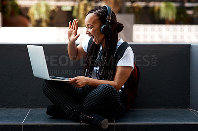 Buy stock photo Shot of an attractive young woman using her laptop to make a video call outdoors