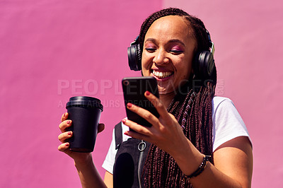 Buy stock photo Cropped shot of an attractive young woman standing against a pink wall and using technology while holding a takeaway coffee