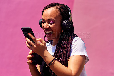 Buy stock photo Cropped shot of an attractive young woman standing against a pink wall and laughing while using technology