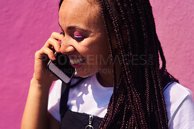 Buy stock photo Cropped shot of an attractive young woman standing against a pink wall alone and talking on her cellphone