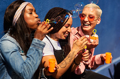 Buy stock photo Cropped shot of three attractive young women sitting against a blue wall together and bonding by blowing bubbles