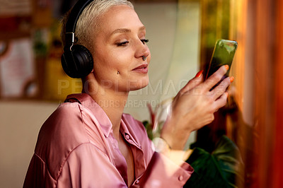 Buy stock photo Shot of an attractive young woman listening to music and using her cellphone inside a local cafe
