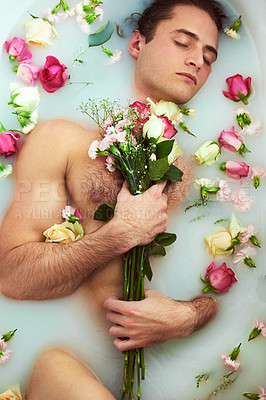 Buy stock photo High angle shot of a handsome young man holding a bouquet while lying in a bathtub full of milky water and flower petals at home
