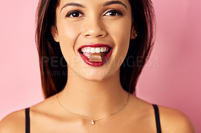 Buy stock photo Studio shot of a beautiful young woman biting a piece of chocolate against a pink background