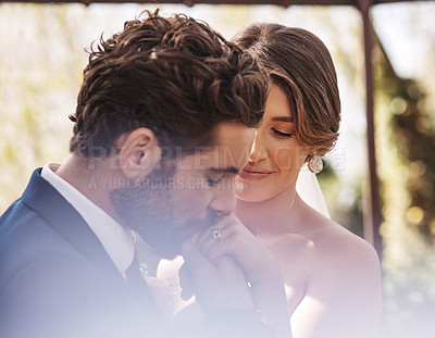 Buy stock photo Cropped shot of an affectionate young bridegroom kissing his bride's hand while standing outdoors on their wedding day