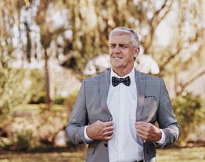 Buy stock photo Cropped shot of a handsome mature bridegroom looking thoughtful while adjusting his suit on his wedding day