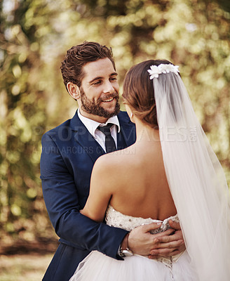 Buy stock photo Cropped shot of an affectionate young bridegroom smiling at his bride while embracing her on their wedding day
