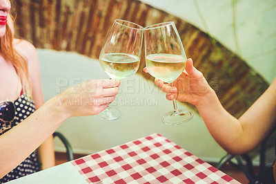 Buy stock photo Cropped shot of two unrecognizable young women having a celebratory toast with wine glasses while being seated at a table in a restaurant