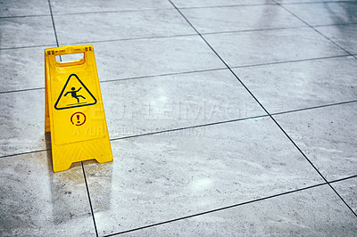Buy stock photo Cropped shot of a sign indicating a wet floor in an empty airport during the day