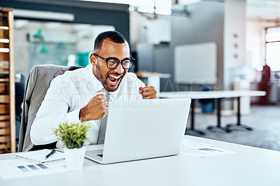 Buy stock photo Cropped shot of a handsome young businessman sitting alone in his office and feeling excited while working on his laptop