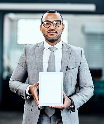 Buy stock photo Cropped portrait of a handsome young businessman standing alone in his office and holding up a blank tablet