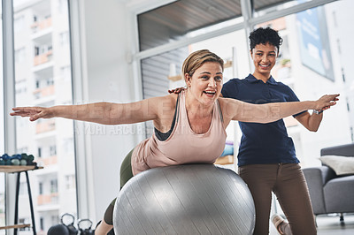Buy stock photo Shot of a mature woman doing rehabilitation and movement exercises with her physiotherapist at a clinic