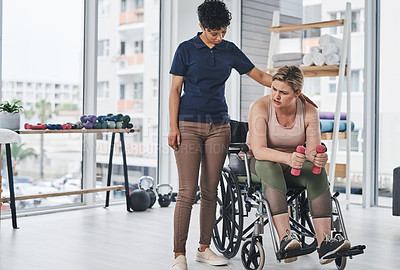 Buy stock photo Full length shot of a young physiotherapist helping her wheelchair bound patient exercise with dumbbells at a clinic