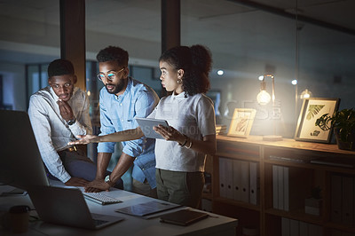 Buy stock photo Cropped shot of a group of young businesspeople having a discussion while using a computer and a digital tablet in an office at night