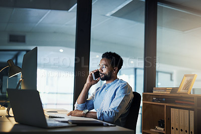 Buy stock photo Shot of a young businessman talking on a cellphone in an office at night
