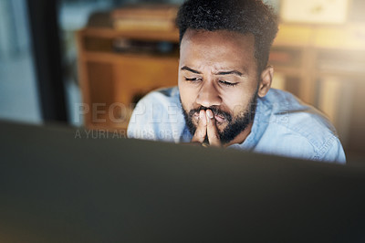 Buy stock photo Shot of a young businessman looking stressed out while working on a computer in an office at night