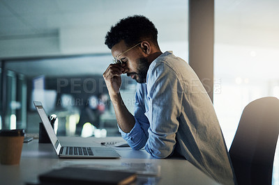 Buy stock photo Shot of a young businessman looking stressed out working in an office at night