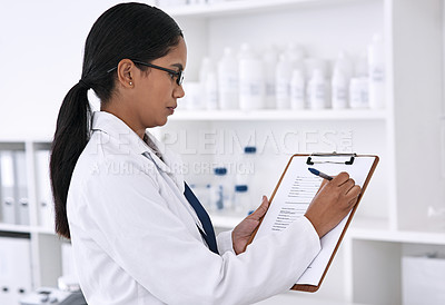 Buy stock photo Cropped shot of an attractive young female scientist working on a clipboard in her laboratory