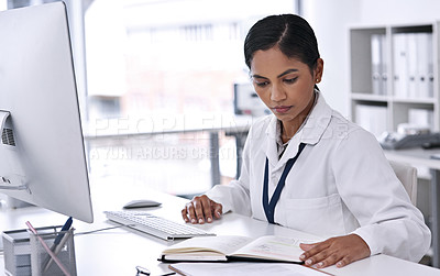 Buy stock photo Cropped shot of an attractive young female scientist working on paperwork in her laboratory