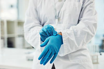Buy stock photo Closeup shot of scientist putting on protective gloves in a lab