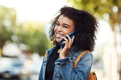 Buy stock photo Shot of an attractive young woman talking on her cellphone while relaxing outdoors in the city