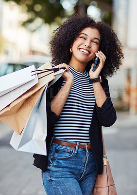 Buy stock photo Shot of an attractive and stylish young woman talking on her cellphone while doing some shopping in the city