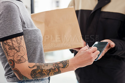Buy stock photo Cropped shot of an unrecognizable woman using a smartphone to sign for her delivery from a male courier at her home