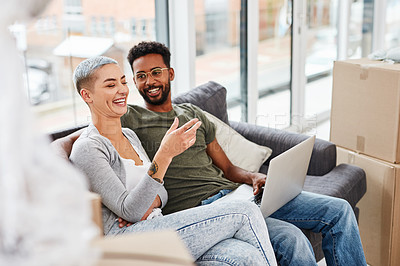 Buy stock photo Shot of a young couple using a laptop while sitting in their new home