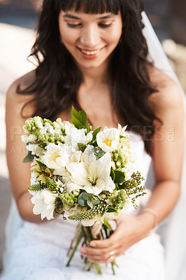 Buy stock photo Cropped shot of a beautiful young bride holding a bouquet of flowers while sitting outdoors on her wedding day