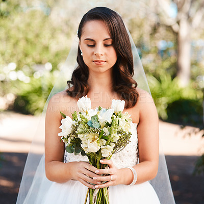 Buy stock photo Cropped shot of a beautiful young bride holding a bouquet of flowers while standing outdoors on her wedding day