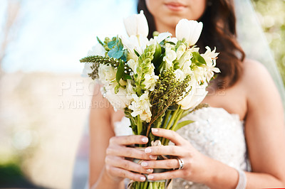 Buy stock photo Cropped shot of an unrecognizable bride holding a bouquet of flowers while standing outdoors on her wedding day