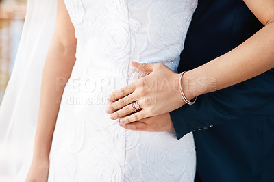 Buy stock photo Cropped shot of an unrecognizable bride showing off her wedding ring while standing with her groom on their wedding day