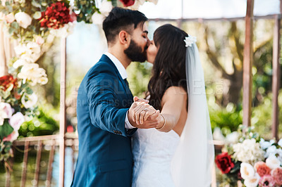 Buy stock photo Cropped shot of an unrecognizable newlywed couple kissing while holding hands on their wedding day