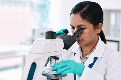 Buy stock photo Cropped shot of an attractive young female scientist looking through a microscope while working in a laboratory