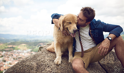 Buy stock photo Cropped shot of a handsome young man sitting on a rock with his golden retriever after a day out hiking