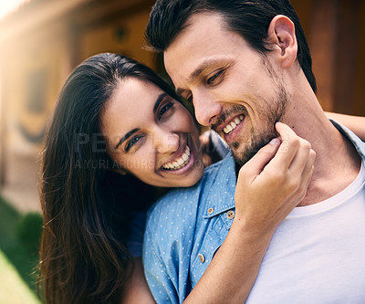 Buy stock photo Cropped shot of an affectionate young woman embracing her husband while standing in their backyard at home