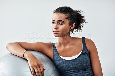 Buy stock photo Studio shot of an attractive young woman taking a break during a workout against a grey background