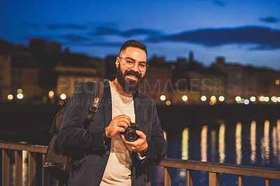 Buy stock photo Cropped portrait of a handsome young man standing on the bridge and holding his camera while touring Italy at night