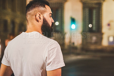 Buy stock photo Cropped shot of a handsome young man walking along the street while sightseeing in Italy at night