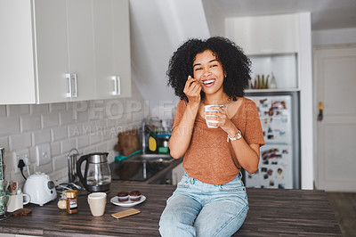 Buy stock photo Shot of a young woman having a tub of yoghurt in the kitchen at home