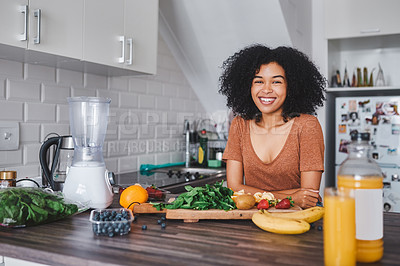 Buy stock photo Shot of a young woman making a healthy snack with fruit at home