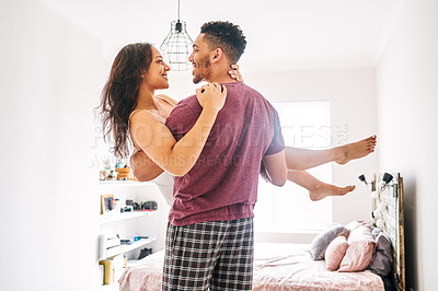 Buy stock photo Shot of a young man romantically carrying his wife in the bedroom