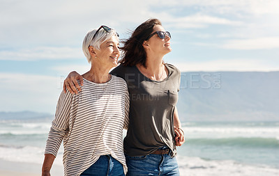 Buy stock photo Shot of a young woman going for a walk along the beach with her elderly mother