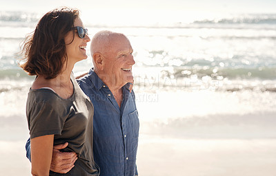 Buy stock photo Shot of a young woman going for a walk along the beach with her elderly father