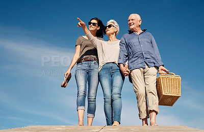 Buy stock photo Shot of a young woman going for a picnic with her elderly parents at the beach
