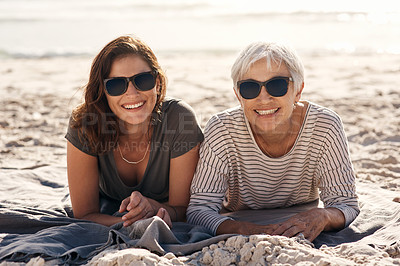 Buy stock photo Shot of a young woman spending quality time with her elderly mother at the beach