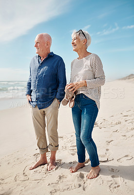Buy stock photo Shot of a senior couple having a fun day at the beach