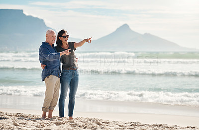 Buy stock photo Shot of a young woman spending quality time with her elderly father at the beach