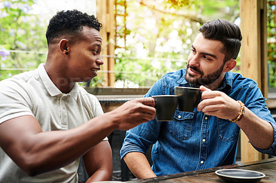 Buy stock photo Shot of two young men toasting with their coffee in a cafe